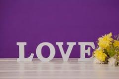 Fleurs jaunes avec des alphabets formant l'amour sur la table Photos libres de droits