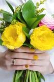 Fleurs jaunes chez des mains de la femme Images stock