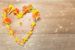 Fleurs jaunes et oranges en forme de coeur sur le fond en bois Image libre de droits