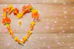 Fleurs jaunes et oranges en forme de coeur sur le fond en bois de vintage Image stock