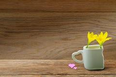 Fleurs jaunes fraîches à la tasse blanche avec le support en forme de coeur et au coeur rose sur le dessus de table en bois grung Image libre de droits