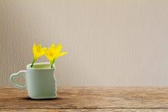 Fleurs jaunes fraîches dans la tasse blanche avec le support en forme de coeur sur la table en bois grunge sur le mur de vintage Photographie stock