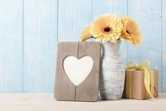 Fleurs jaunes fraîches de gerbera, boîte-cadeau et photo en forme de coeur franc Photos stock