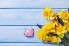 Fleurs jaunes lumineuses de jonquilles et coeur rose décoratif dessus Image stock