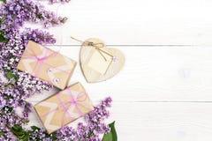 Fleurs lilas avec des boîte-cadeau et cadre de coeur sur le fond en bois blanc Images stock