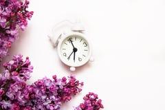 Fleurs lilas avec le réveil minuscule de cru sur le fond blanc Concept de matin de ressort Vue sup?rieure, configuration plate image stock