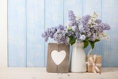 Fleurs lilas dans la cruche, le boîte-cadeau et le cadre en forme de coeur Photos libres de droits