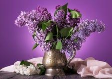 Fleurs lilas dans un vieux vase, près du brin des fleurs blanches sur le fond du tissu fin photos stock