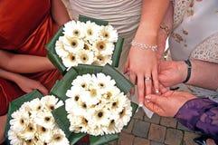 Fleurs, mains et anneaux de jeune mariée Photo stock