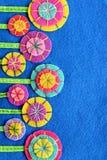Fleurs multicolores sur une feuille bleue de feutre Conception et décor de DIY Cousez sur les fleurs lumineuses Fond de vacances images libres de droits