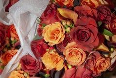 Fleurs nuptiales rouges et oranges dans le panier images stock