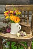 Fleurs, oignons et un fer sur une vieille chaise Photo stock