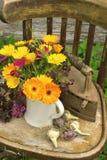 Fleurs, oignons et un fer sur une vieille chaise Image stock