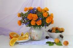 Fleurs oranges en vase et fruits Image libre de droits