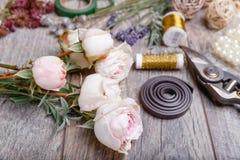 Fleurs, outils, rubans, roses, lavande, herbes, verts sur la table du ` s de fleuriste dans le flowershop Table rustique en bois  Photo libre de droits