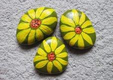 Fleurs peintes sur des pierres Images stock