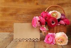 Fleurs roses à côté de carte vide, sur la table en bois Image stock