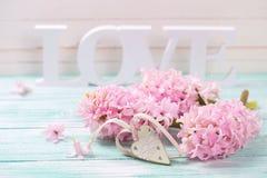 Fleurs roses, amour en bois de mot et coeur décoratif sur le turquoi Image stock