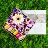 Fleurs roses, blanches, pourpres et macarons colorés dans un boîte-cadeau Photo stock