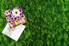 Fleurs roses, blanches, pourpres et macarons colorés dans un boîte-cadeau Photos stock