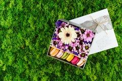 Fleurs roses, blanches, pourpres et macarons colorés dans un boîte-cadeau Photographie stock