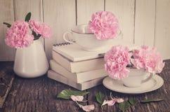 Fleurs roses d'oeillet dans la tasse de thé blanche Image stock