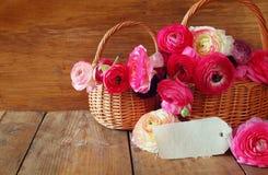 Fleurs roses dans le panier à côté de la carte vide, sur la table en bois Image libre de droits