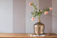 Fleurs roses dans le vase à chrome sur la fourrure avec la texture rayée de fond Images libres de droits