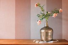 Fleurs roses dans le vase à chrome sur la fourrure avec la texture rayée rose de fond Image stock