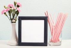 Fleurs roses dans un vase, des pailles de papier et un cadre vide Photographie stock