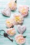 Fleurs roses de pivoines, deux coeurs décoratifs et clé sur le turquo Photos stock