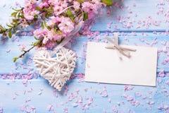 Fleurs roses de Sakura, coeur décoratif et Empty tag sur l'OE bleu Photo stock