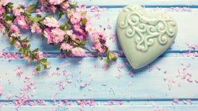 Fleurs roses de Sakura et coeur décoratif de turquoise sur W bleu Photographie stock