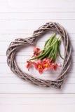Fleurs roses de tulipes et coeur décoratif sur la planche en bois blanche Images libres de droits