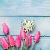 Fleurs roses de tulipes et coeur décoratif sur le backgro en bois bleu Photographie stock