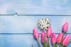 Fleurs roses de tulipes et coeur décoratif sur le backgro en bois bleu Photos libres de droits