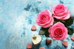 Fleurs roses des roses et des coeurs de sucrerie pour des valentines Photographie stock libre de droits