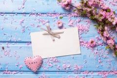 Fleurs roses, Empty tag et coeur de Sakura sur les planches en bois bleues Images stock