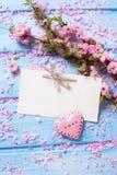 Fleurs roses, Empty tag et coeur de Sakura sur les planches en bois bleues Image stock