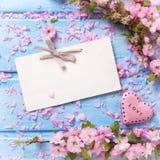 Fleurs roses, Empty tag et coeur de Sakura sur les planches en bois bleues Images libres de droits