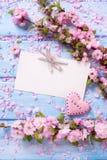 Fleurs roses, Empty tag et coeur de Sakura sur les planches en bois bleues Photographie stock libre de droits
