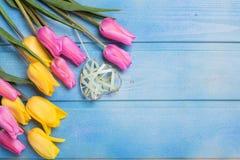 Fleurs roses et jaunes de tulipes et coeur décoratif sur l'OE bleu Image libre de droits