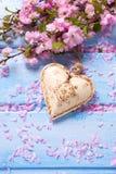 Fleurs roses fraîches de Sakura et coeur décoratif sur p en bois bleu Image libre de droits