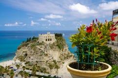 Fleurs rouges dans le pot de fleurs avec le vallon brouillé Isola de Santa Maria d'église de sanctuaire de monastère sur la roche photo libre de droits