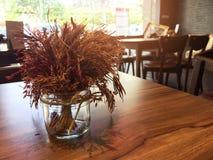 Fleurs sèches dans un verre clair à un café Photos stock
