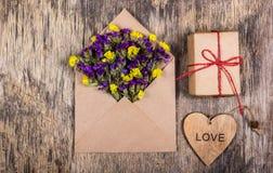Fleurs sèches de champ sous enveloppe de papier Lettre romantique Un coeur en bois photos libres de droits