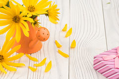 Fleurs sauvages dans une boîte d'arrosage avec un boîte-cadeau sur une table en bois Image stock