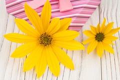 Fleurs sauvages dans une boîte d'arrosage avec un boîte-cadeau sur une table en bois Photographie stock libre de droits