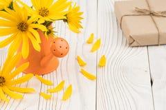 Fleurs sauvages dans une boîte d'arrosage avec un boîte-cadeau sur une table en bois Photographie stock