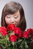 Fleurs sentantes de beau femme asiatique Photographie stock